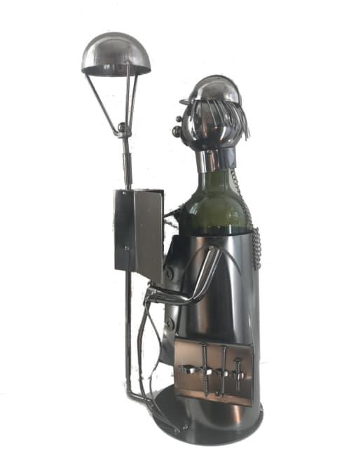 Kovový stojan na víno, motiv elektrikář s lampou